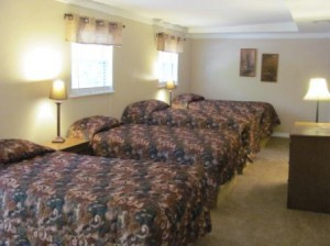 This bedroom has four twin beds and has a sitting area at the end.  Lots of room for the kids.